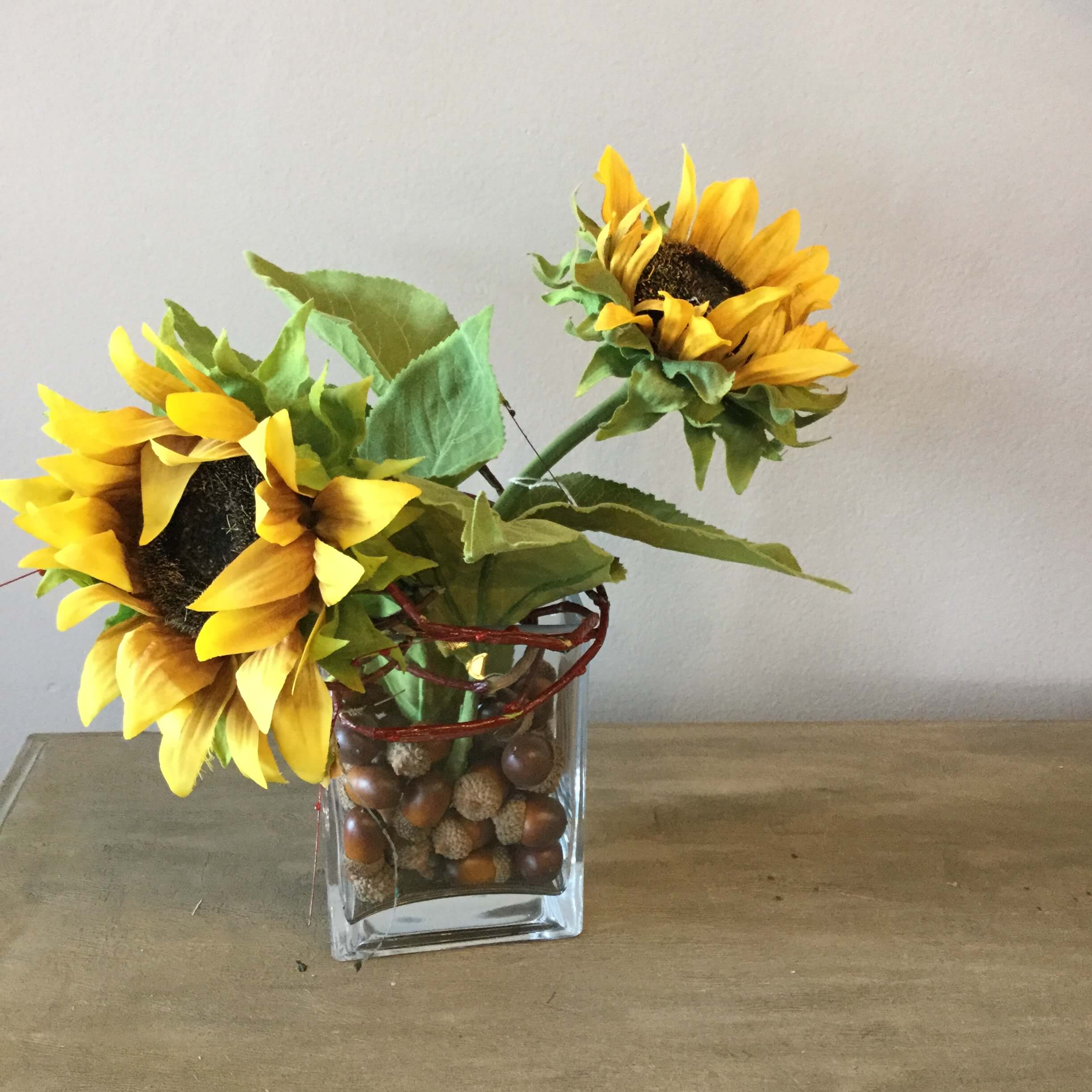 11 Yellow Sunflowers In Glass Vase With Acorns And Vine Ps